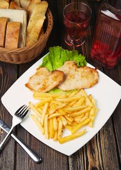 Pepite di petto di pollo arrosto con patatine fritte nel piatto bianco.