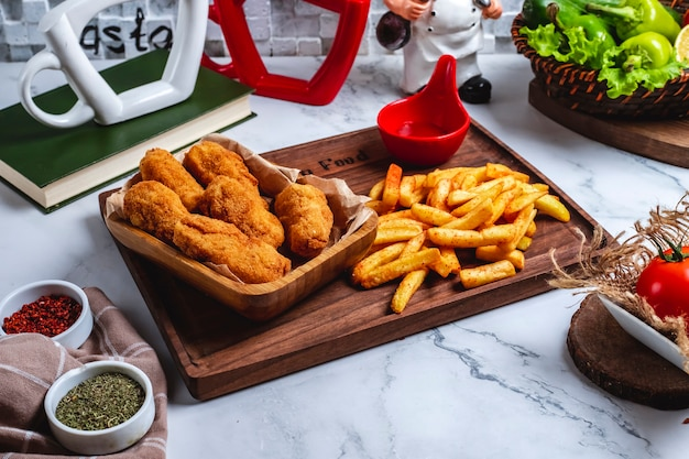 Pepite di pollo di vista laterale con patate fritte e ketchup sul bordo