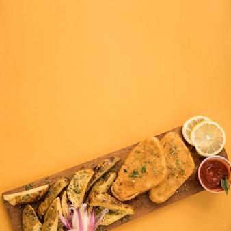 Pepite di pollo e spicchi di patate disposti su tavola di legno