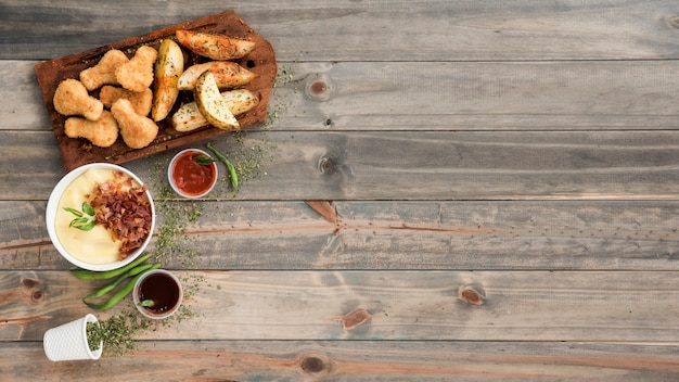 Pepite di pollo e spicchi di patate su tavola di legno