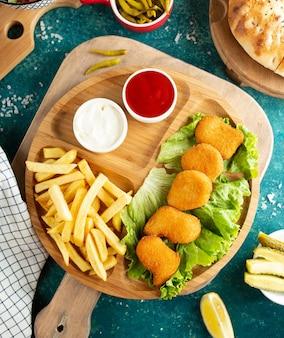 Pepite di pollo fritto con la vista superiore delle patate fritte