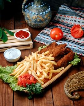 Pepite di pollo fritto con patate fritte sul tavolo