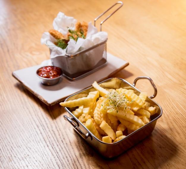 Pepite di pollo fritto con patatine fritte e salsa di pomodoro. ristorante.