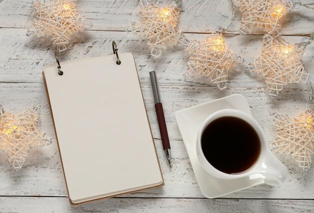 Per fare la lista delle vacanze invernali. lista della spesa tazza di tè e ghirlanda luminosa. piani per natale blocco note bianco e ghirlanda luminosa su bianco shabby chic. umore invernale