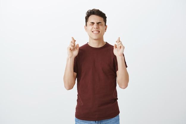 Per favore ascolta le mie preghiere, dio. ritratto di ragazzo bello intenso preoccupato in maglietta rossa