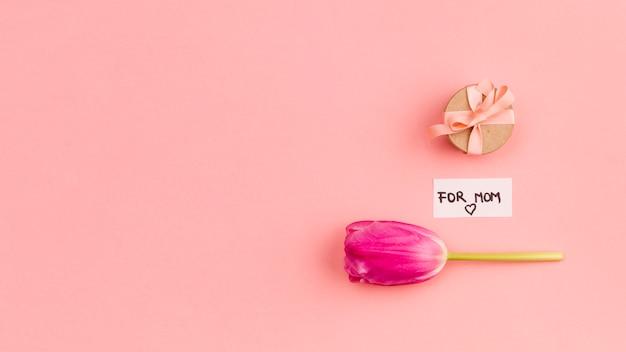 Per il titolo di mamma su carta vicino presente e fiore