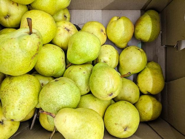 Pera verde in scatola. varietà di pere fresche coltivate nel negozio.