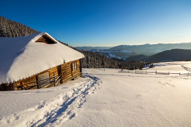 Percorso di impronta umana in bianco neve profonda che conduce alla piccola vecchia capanna di pastore in legno abbandonato nella valle di montagna, fores abete
