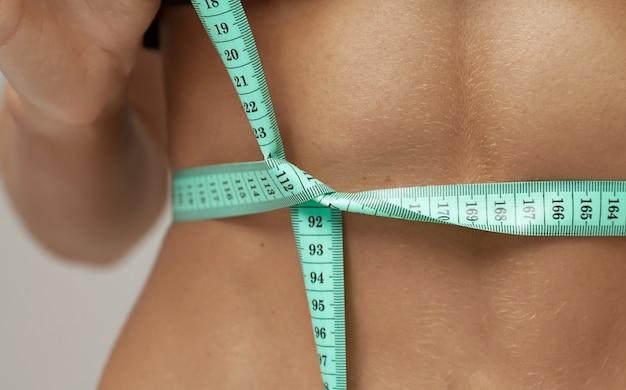 Perdita di peso, corpo snello, concetto di stile di vita sano. ragazza adatta di forma fisica che misura il suo giro vita con nastro adesivo di misura su gray