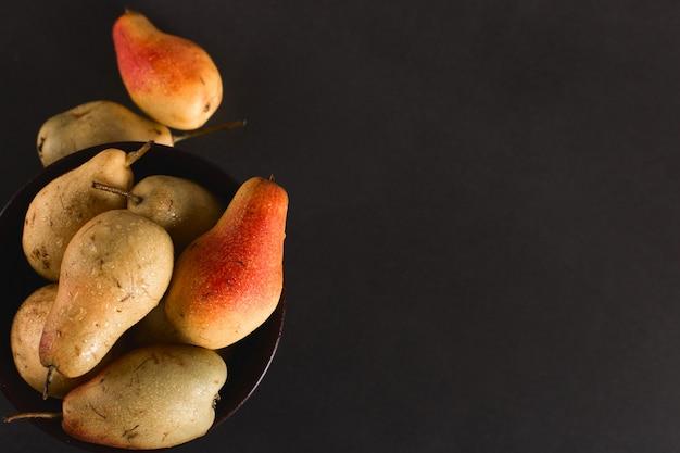 Pere appetitose succose fresche in una ciotola marrone, estate, copyspace.