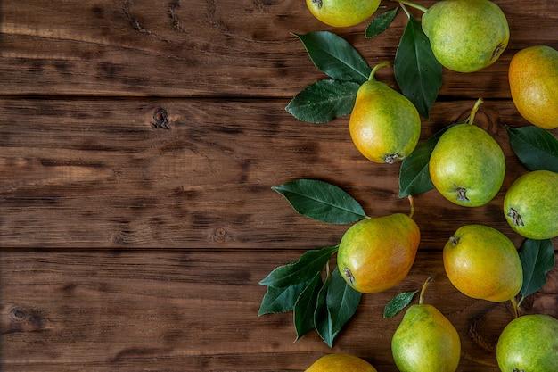 Pere fresche con le foglie su una tavola di legno