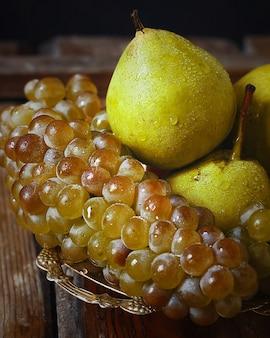 Pere fresche e uva verde. concetto di natura autunnale.