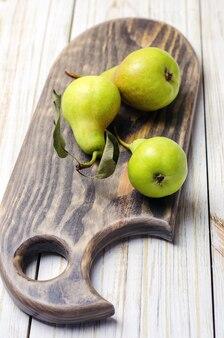 Pere fresche sul tagliere di legno marrone.