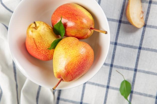 Pere organiche che si stendono su un panno da cucina leggermente punteggiato