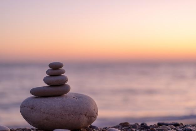Perfetto equilibrio di pila di ciottoli in riva al mare verso il tramonto