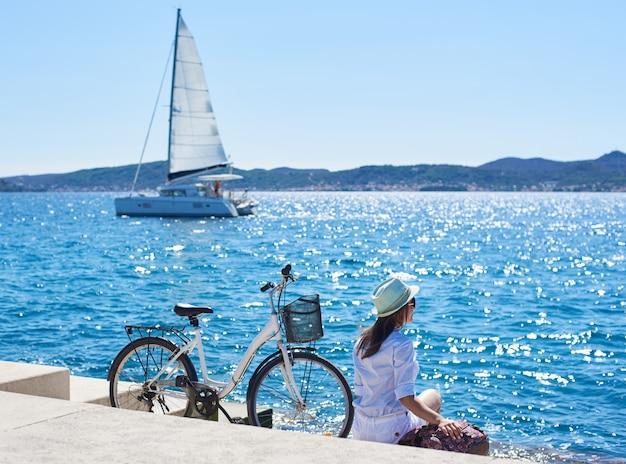 Perfetto paesaggio estivo in una luminosa giornata di sole. punto di vista posteriore del turista femminile con lo zaino che si siede alla bicicletta sul marciapiede pavimentato sotto il chiaro cielo blu. nave a vela in acque azzurre