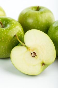 Perfetto succoso dolce fresco fresco delle mele verdi isolato sullo scrittorio bianco