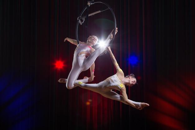 Performance di acrobata da attrice circense. due ragazze eseguono elementi acrobatici nell'anello dell'aria.