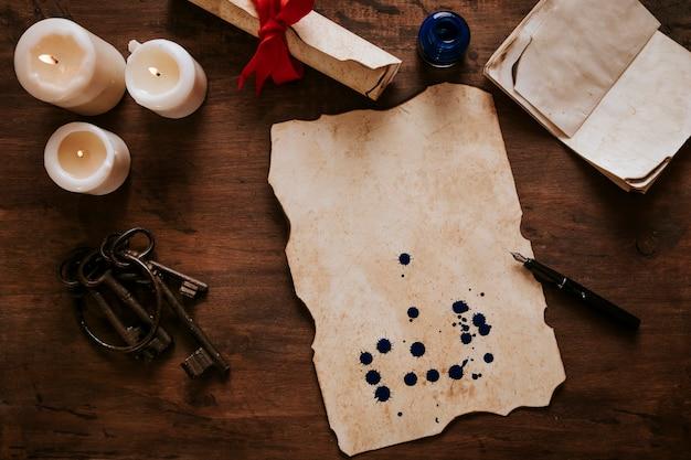 Pergamena con macchie di inchiostro vicino a candele e chiavi
