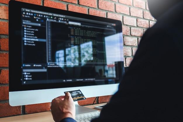 Pericoloso hacker incappucciato con carta di credito digitando dati errati nel sistema online del computer