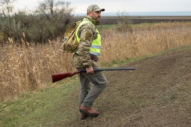 Periodo di caccia, stagione autunnale aperta. un cacciatore con una pistola in mano in abiti da caccia nella foresta di autunno in cerca di un trofeo.