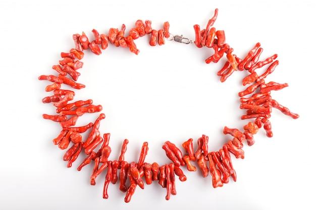 Perle di corallo rosso isolate su fondo bianco