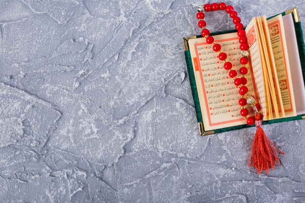 Perle rosse luminose del rosario in un kuran santo aperto sopra il contesto strutturato concreto