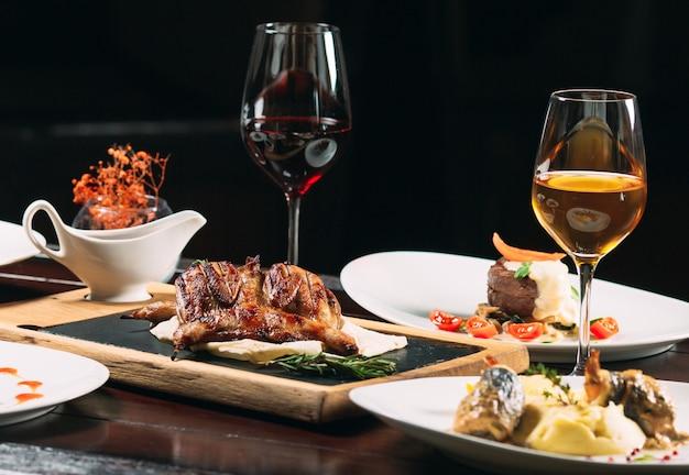 Pernice alla griglia, spigola, tartaro. diversi piatti sul tavolo al ristorante.