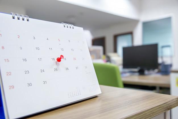 Perno di colore rosso sul concetto di calendario del pianificatore di eventi.