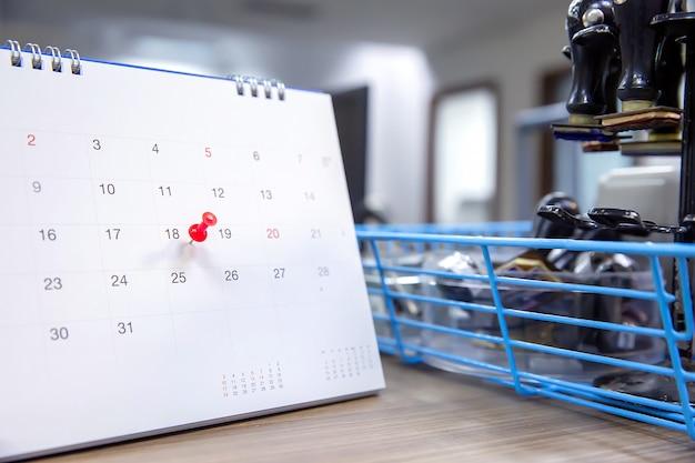 Perno e calendario di colore rosso sullo scrittorio per il pianificatore di eventi aziendali.
