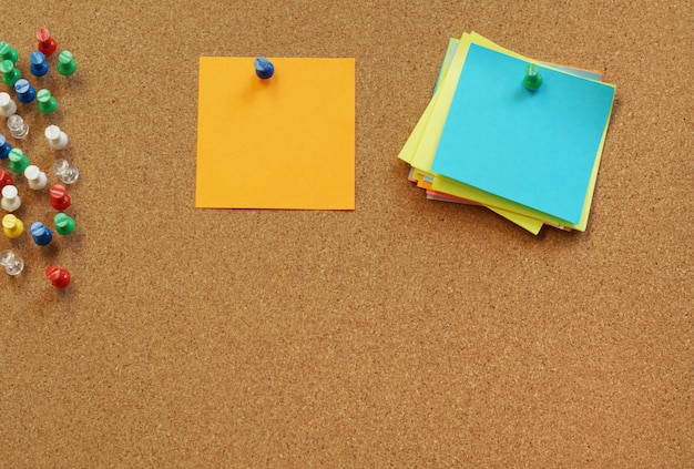 Perno in bianco puzzolente delle note sul bordo del sughero. tavola di sughero con note vuote.