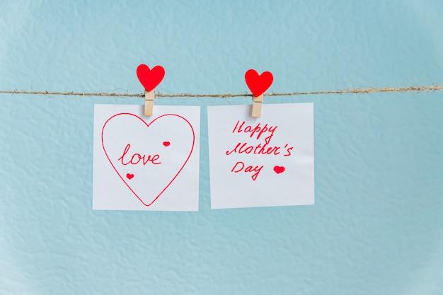Perno rosso dei cuori di amore che appende sul cavo naturale contro il fondo blu. iscrizione felice di festa della mamma sul pezzo di carta.