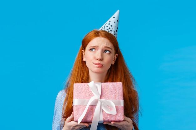 Perplessa e indecisa, la ragazza rossa vuole un presente aperto, pensando con espressione preoccupata, tenendo in mano una confezione regalo rosa, indossa un berretto da compleanno, guarda lateralmente, parete blu