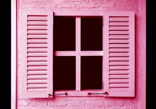 Persiane colorate rosa sul muro di mattoni rosa