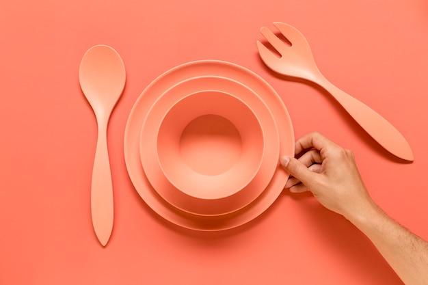 Persona anonima che mette stoviglie rosa sul tavolo
