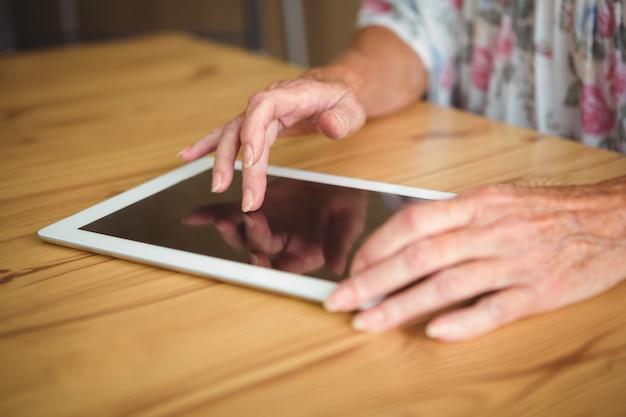 Persona anziana che tocca una compressa digitale