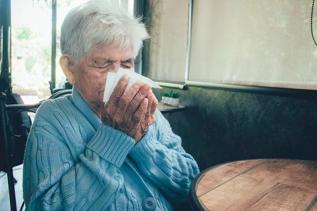 Persona anziana che tossisce coprendo la bocca con un tessuto su un interno della casa. ha influenza, sintomi allergici, bronchite acuta, infezioni polmonari o polmonite.