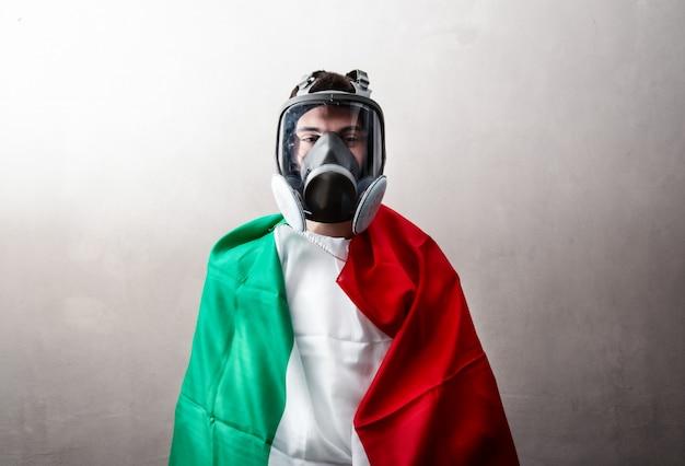 Persona avvolta in una bandiera italiana con maschera antibatterica