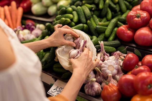 Persona che acquista l'aglio dalla vista alta del mercato
