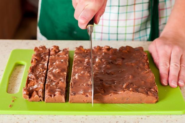 Persona che affetta il fondente di cioccolato di natale