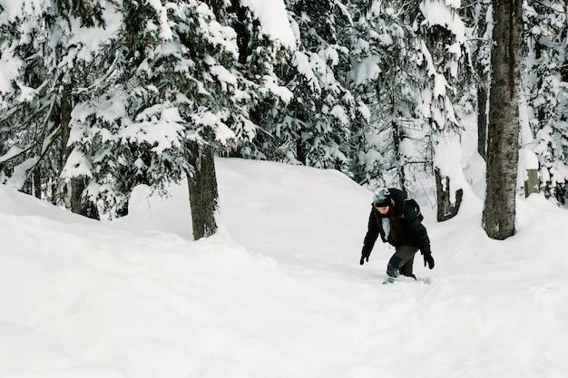 Persona che cammina nella foresta nevosa