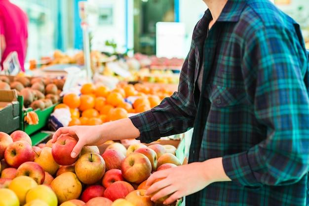 Persona che compra frutta e verdura