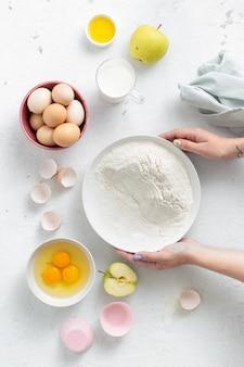 Persona che cucina dessert. mani delle donne che preparano vista superiore della torta di mele. ingredienti alimentari da forno