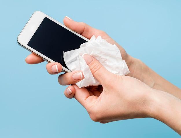 Persona che disinfetta lo smartphone
