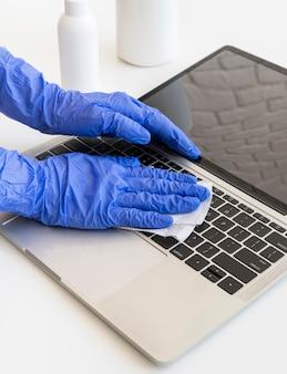 Persona che disinfetta un computer portatile