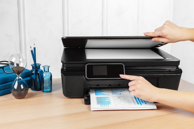 Persona che fa copie sulla fotocopiatrice in ufficio