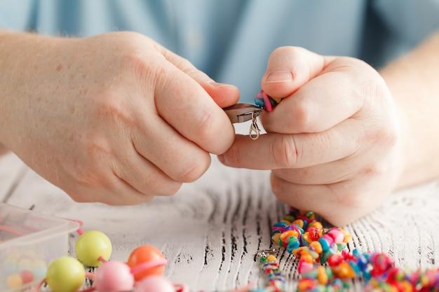 Persona che fa orecchini da perline colorate e aghi