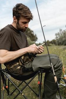 Persona che fissa un amo da pesca
