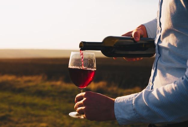 Persona che ha versato vino rosso in un bicchiere al tramonto