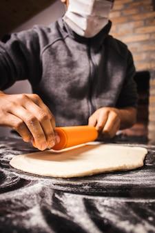 Persona che indossa una maschera e prepara l'impasto per fare la pizza